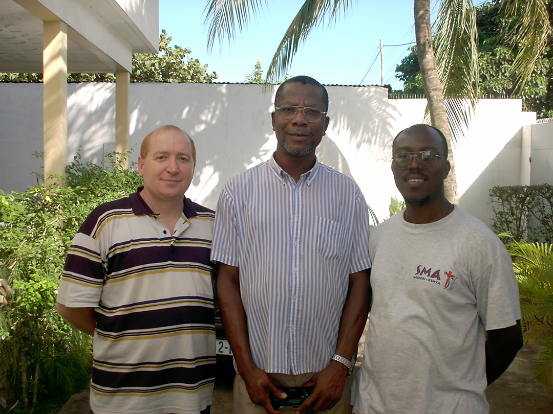 Michael Adrie surrounded by Tony Porcellato (left) and Innocent Okozi.